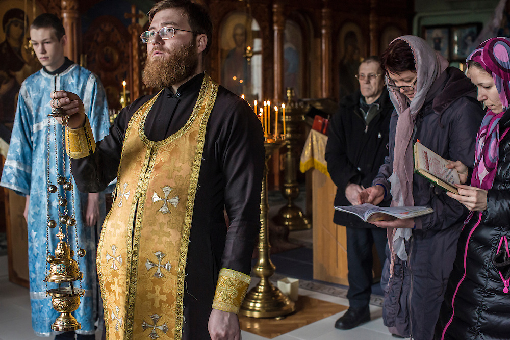 Priest Rostislav Morozov, second from left, leads parishoners in a service at the Church of Our Lady of Kazan on Sunday, February 14, 2016 in Pervomaiske, Ukraine.