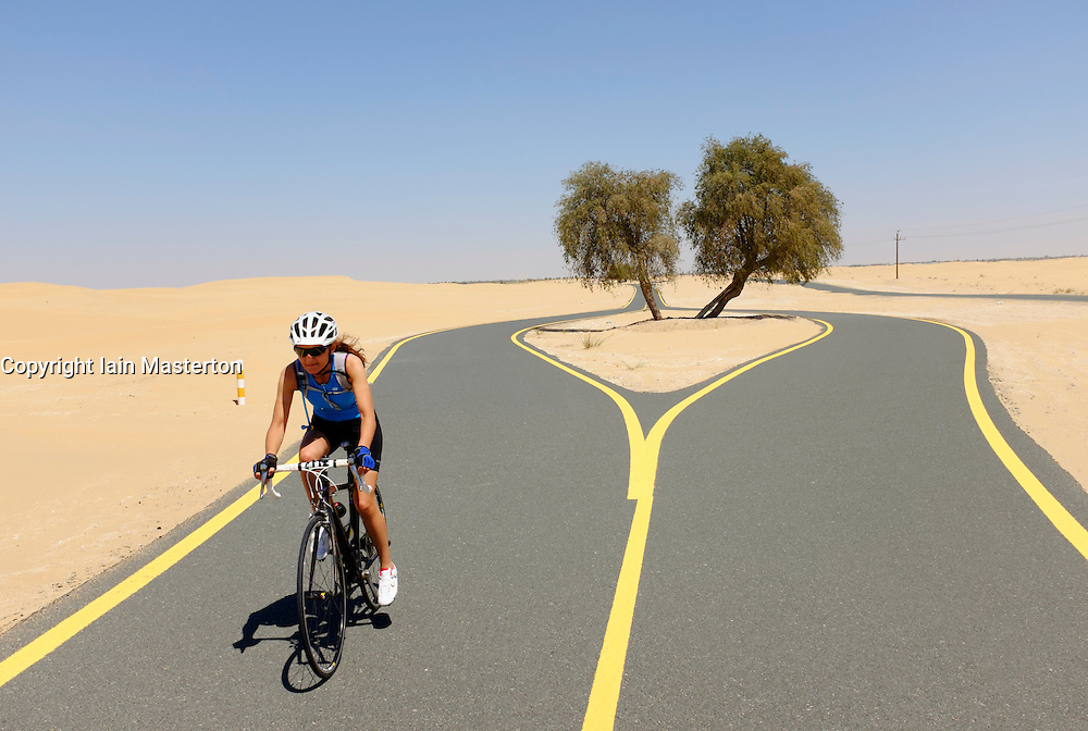 Female cyclist of new desert cycle track at Al Qudra in Dubai United Arab Emirates