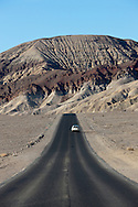 A minivan drives on a road north from Badwater through Death Valley National Park, California