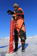 Ice physicist Sebastian Gerland (Norwegian Polar Institute)cores fjord ice to collect data about the ice and its role in the carbon cycle; Kongsfjord, Svalbard, Norway.