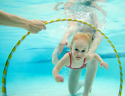 NEWS&GUIDE PHOTO / PRICE CHAMBERS.Maren Tattersall, 2, swims through a hoop during Mary Pat Walker's baby swimming class at the Teton County Recreation Center on Thursday. Small groups of children and their parents use several fun exercises to have the little ones holding their breath and paddling around in just a few weeks..
