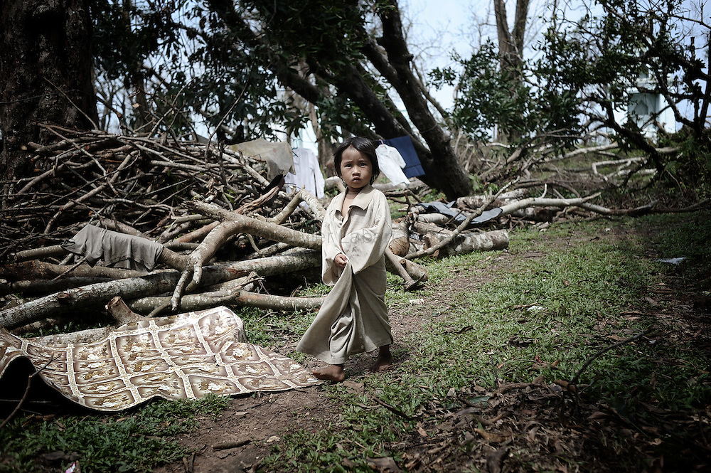 A young girl affected by cyclone Nargis walks near a monastry where she and her family found shelter near Kyauktan in the delta region south of Yangon on May 16, 2008. State television on May 16, 2008 put the latest toll at 77,738 dead and 55,917 missing from Cyclone Nargis, which barrelled into the country on May 2-3, wiping away entire villages and submerging swathes of land under flood waters.