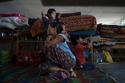 Resonla Rengma and her 3 children, of the Khanari Village, rest in their makeshift home in the Borpathar High School. The benches used as walls between families contain all of the possessions they could carry out of their village. They eat, sleep, and play on the same thinly matted 8 foot by 8 foot section of concrete. Image © Jonah Markowitz/Falcon Photo Agency