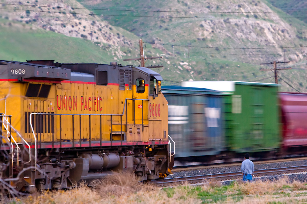 The conductor of an eastbound Union Pacific freight is down on the ground inspecting a passing BNSF westbound train at Caliente, CA, in the Tehachapi Mountains.
