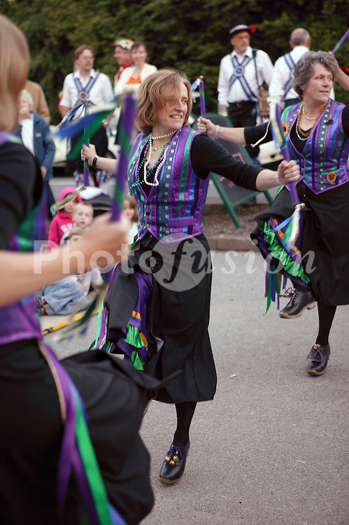 Group of Morris dancers performing dance outside village pub,