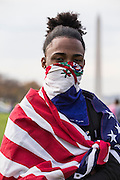 WASHINGTON, USA - November 15: Alex Martinez, 16, a student from Bell Multicultural High School, wears an American flag around his shoulders and a Dominican Republic bandana around his face as he marches with thousands of area High School students along the National Mall to the Washington Monument to protest President-elect Donald Trump after leaving their classes early in Washington, USA on November 15, 2016.