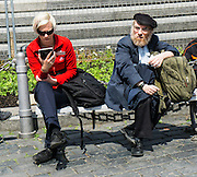 Two people sharing a bench in one of Prague's squares. Both are travellers. Both seem to completely ignore each other.