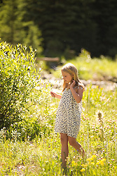 little blonde girl in a sun lit field of wildflowers by a stream in the woods