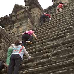 A group of Korean tourists scale the steep crumbling stairs of the Inner temple at Angkor Wat, the largest and most famous of the many ancient temples of the Khmer Empire near Siem Reap, Cambodia.  In August of 2007 an international team of researchers concluded that Angkor, a Unesco World Heritage Site, had been the largest preindustrial city in the world with an urban sprawl of 1,150 square miles.