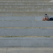 A female college student uses her laptop while studying in an outdoor amphitheater.