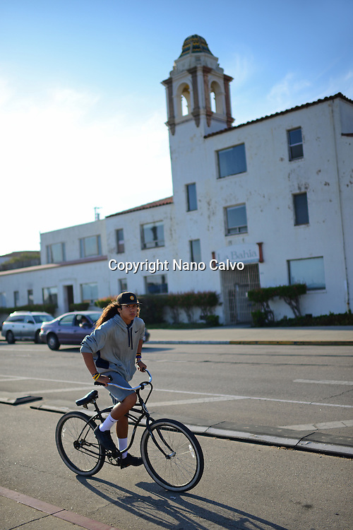 Teenager riding his bicycle in Santa Cruz boardwalk, California.