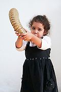 Young girl of three blows a Shofar Cutout on white background Model Release Available