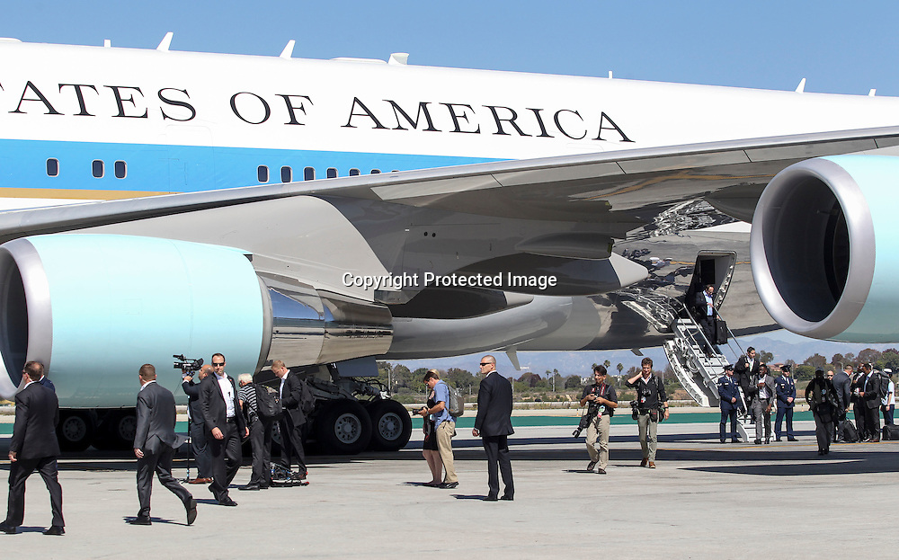 Members of the White House media travel pool and White staff walks out the Air Force One ahead President Barack Obama's arrival at Los Angeles International Airport in Los Angeles on Saturday, Oct. 10, 2015. (AP Photo/Ringo H.W. Chiu)