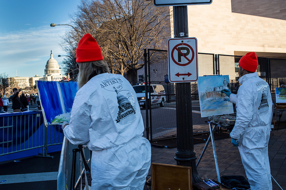 Stephanie Wurt, left, of Powhatan, VA, and Andrew Purchin of Santa Cruz, CA, with the organization A Thousand Artists, paint along Pennsylvania Avenue on Sunday, January 20, 2013 in Washington, DC.