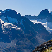 Glaciers cling to the schist peaks of the Darran Mountains high above Hollyford Valley in Fiordland National Park, as seen from atop Conical Hill, on the Routeburn Track, South Island, New Zealand. In 1990, UNESCO honored Te Wahipounamu - South West New Zealand as a World Heritage Area. Panorama stitched from 5 overlapping photos.