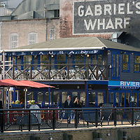 UK. London. People enjoying the sunshine at Gabriel's Wharf on London's Bankside with the London Eye behind..