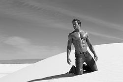 man without a shirt kneeling on a sand dune in White Sands, NM