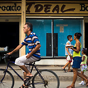 "People go past a store with empty displays called ""Market Ideal"" in Baracoa, Cuba on Saturday July 12, 2008."