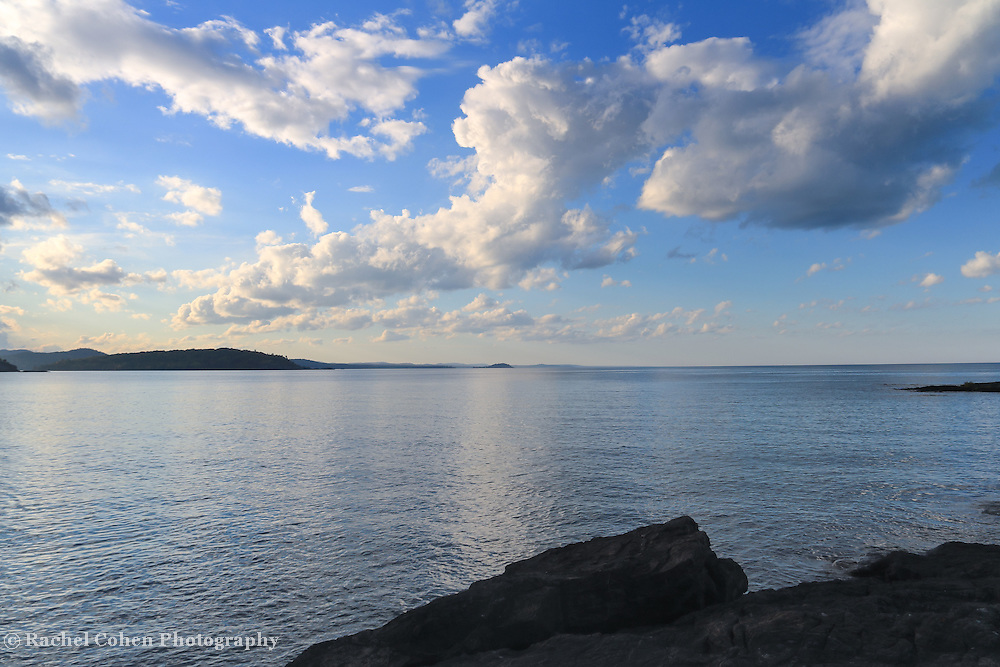 &quot;On the Edge&quot; <br /> <br /> Stand on the edge of jagged rocks on the shores of Lake Superior on Presque Isle Park in Marquette, Michigan! Enjoy still waters, blue skies and wonderful puffy white clouds!