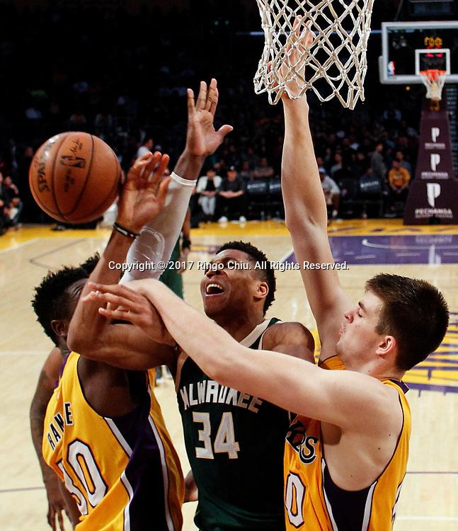 3月17日,密尔沃基雄鹿队球员扬尼斯-阿德托昆博(中)在比賽中上篮受阻。 当日,在2016-2017赛季NBA常规赛中,洛杉矶湖人队主场以103比107不敌密尔沃基雄鹿队。 新华社发 (赵汉荣摄)<br /> Milwaukee Bucks forward Giannis Antetokounmpo (#34) gets fouled by Los Angeles Lakers during an NBA basketball game, Friday, March 17, 2017.(Photo by Ringo Chiu/PHOTOFORMULA.com)<br /> <br /> Usage Notes: This content is intended for editorial use only. For other uses, additional clearances may be required.