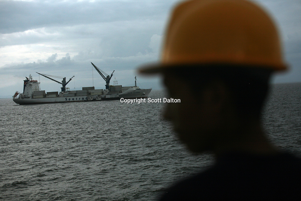 A security officer keeps watch from the deck of one ship as another one gets loaded with Colombian bananas in the Gulf of Turbo, along Colombia?s northern coast, on July 10, 2007. Colombia?s banana region has long a stronghold for illegal armed groups who apparently funded their wars by taxing the banana industry. American banana executives of the Cincinnati-based fruit giant Chiquita have acknowledged making monthly protection payments for six years to illegal groups that killed thousands of people. (Photo/Scott Dalton)