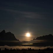 The full moon begins to set behind the Teton Range as fog forms at night in Grand Teton National Park, Wyoming. The Teton Range is the youngest mountain range in the Rocky Mountains, forming between 6 to 9 million years ago. The peaks are fault-block mountains, caused by tilting along the fault where they formed. Grand Teton, visible to the left of the moon, is 13,775 feet (4,199 meters) high. Grand Teton National Park contains another nine peaks that are at least 12,000 feet (3,658 meters) above sea level.