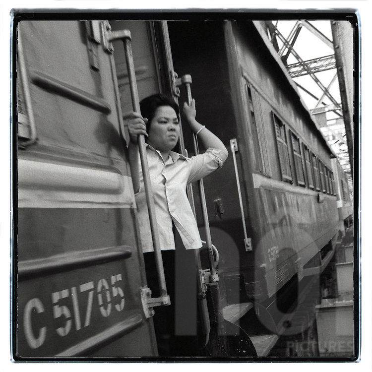While the train is crossing Long Bien bridge, a woman stands in a doorway of the wagon to get some air despite the risk of falling, Hanoi, Vietnam, Southeast Asia