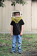 MELISSA LYTTLE | Times<br /> The Harold P. Curtis Honey Co. in LaBelle, Fla. has been raising bees and collecting honey for six generations. The baby of the family, Caden Pratt, 4, wears a veil while playing around with the bee hives in the back of his family's store on March 25, 2014. Caden says he doesn't like being stung, but he's not afraid of the bees either.