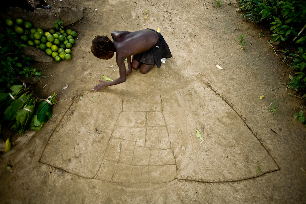A girl draws in the dirt the floorplan of her ideal home.