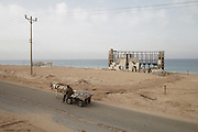 A man leads his donkey and rubble filled cart along the coast road past the former al-Waha Resort after collecting the material near Gaza's northern border with Israeli. The rubble fetches 50 Shekels (approx EUR10) per tonne and is used in the production of concrete.