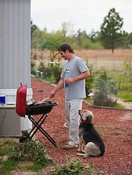 Man outdoors cooking on a grill with dog watching
