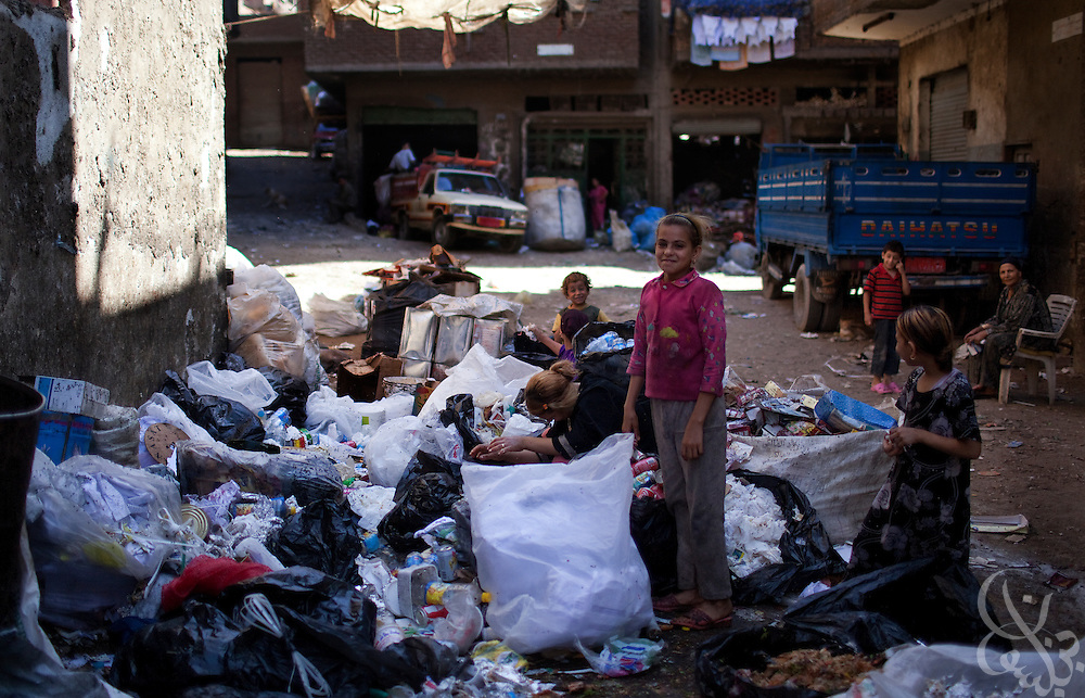 """Egyptian women and children sort garbage into organic and inorganic piles in the Manshiyet Nasr neighborhood of Cairo, Egypt June 5, 2009. The majority coptic christian garbage collectors, known as """"zabbaleen"""", (""""garbage people"""" in arabic), recently have had to adapt to a new way of working after the Egyptian government confiscated and killed all the pigs in their area. Pigs are important to the zabbaleen, since the pigs are used to dispose of all the organic bits of trash collected."""