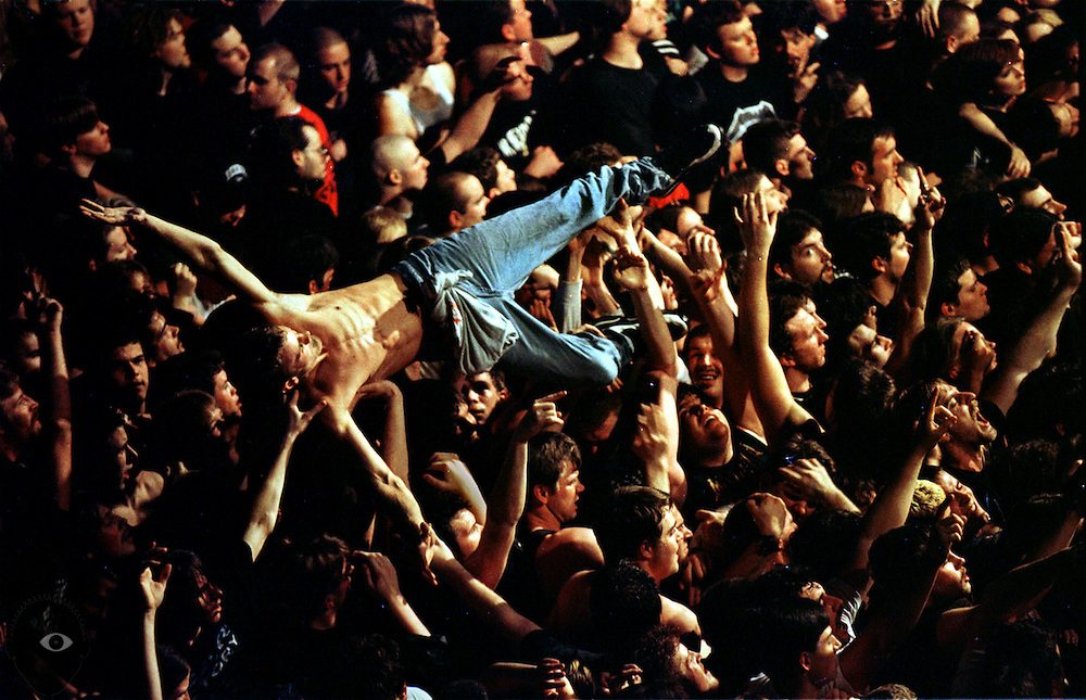 A crowd surfer is hoisted atop the masses during a concert.