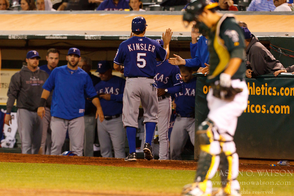 September 20, 2011; Oakland, CA, USA;  Texas Rangers second baseman Ian Kinsler (5) is congratulated by teammates in the dugout after scoring a run past Oakland Athletics catcher Kurt Suzuki (front) during the eighth inning at O.co Coliseum.