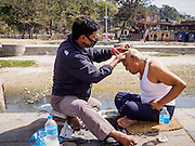 07 MARCH 2017 - KATHMANDU, NEPAL: A man has his head shaved onthe ghats of the Bagmati River at Pashupatinath, a complex of important Hindu temples in Kathmandu, before meeting with a Hindu priest on the one year anniversary of the death of a family member. The Bagmati River runs through the complex. It is Nepal's most holy river, and this stretch of the river is like Varanasi in India. The river bank is lined with cremation ghats. Many Hindus, from both Nepal and India, make pilgrimages to Pashupatinath. It is traditional in Nepali Hinduism to mark the one year anniversary of a loved ones death to meet with a Hindu priest.      PHOTO BY JACK KURTZ