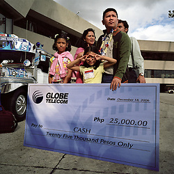 With the sponsorship of Globe Telecom, a family received 25,000 pesos from the Overseas Workers Welfare Administration, OWWA, in Manila, Philippines on Dec. 2006. OWWA held several holiday events giving out many prizes to workers throughout the Philippines to welcome the roughly 120,000 OFWs that came home for the Christmas season. Even President Gloria Macapagal-Arroyo took time out of her busy schedule to greet returning OFWs at the Ninoy Aquino International Airport.