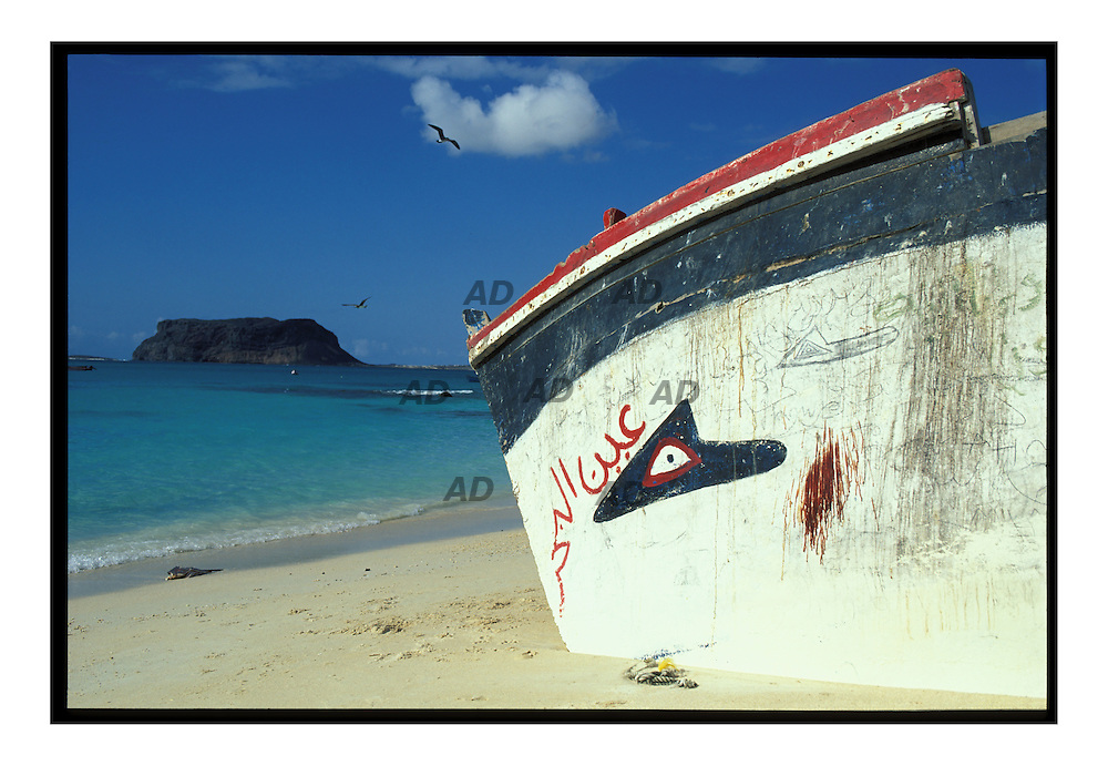Una vecchia barca, sullo sfondo il promontorio di Bir Ali.