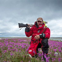 Canada, Manitoba, Photographer Paul Souders carries shotgun with noise-making shells as polar bear protection at Hubbart Point on Hudson Bay