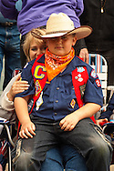 Cub Scout with mom watches Miles City Bucking Horse Sale Parade, Montana