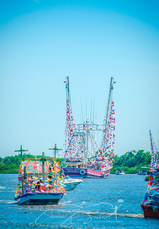 Decorated boats travel down the bayou during the 66th annual Blessing of the Fleet down the bayou during the 66th annual Blessing of the Fleet in Bayou La Batre, Alabama, May 3, 2015. The first fleet blessing was held by St. Margaret's Catholic Church in 1949, carrying on a long European tradition of asking God's favor for a bountiful seafood harvest and protection from the perils of the sea. The highlight of the event is a blessing of the boats by the local Catholic archbishop and the tossing of a ceremonial wreath in memory of those who have lost their lives at sea. The event also includes a land parade and a parade of decorated boats that slowly cruise through the bayou. (Photo by Carmen K. Sisson/Cloudybright)