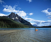 A lone canoeist wades to shore on Emerald Lake in Yoho National Park, British Columbia, Canada.