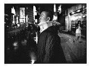 Man with neck brace on wet street, Tokyo, Japan.