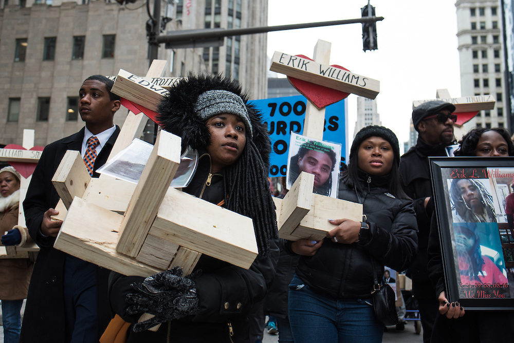 People carry over 750 wooden crosses dedicated to lives lost to violence during 2016 in Chicago during a peace march on Michigan Avenue in Chicago on December 31, 2016.
