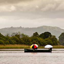A small boat with fisherman holding colored umbrellas passes by on the lake in a gloomy rainy day. On the background the green landscape of the Lake District in the UK.