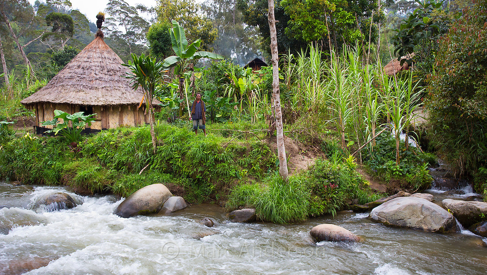 Woman and her traditional village home by a fast flowing river in the Papua New Guniea Highlands.