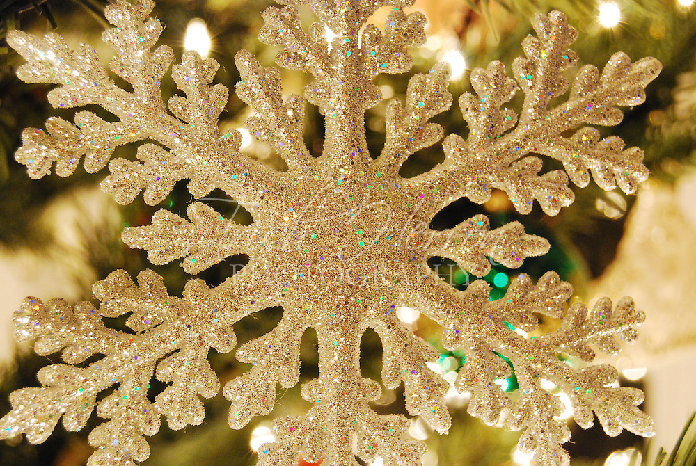 A sparkly snowflake ornament glistens in the lights on a Christmas tree.