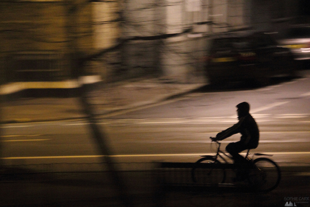 Boy wearing hooded top (hoodie) on bicycle at night, along the New King's Road in Parsons Green, South-West London