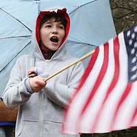 (Wellesley, MA - 4/20/15) Oliver Nosal, 12, of Bedford, waves an American flag as he cheers for runners along the route of the Boston Marathon, Monday, April 20, 2015. Staff photo by Angela Rowlings.