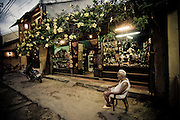 An elderly Vietnamese man people watches in front of his store in the Old Quarter, Hoi An, Vietnam, Southeast Asia.