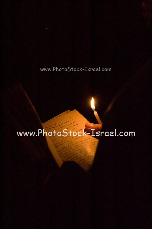 Interior of the church of the Holy Sepulchre, Old city, Jerusalem, Israel Praying by candle light